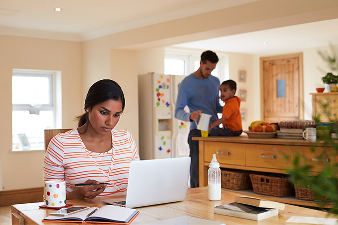 Family In Kitchen With Mom taking online course